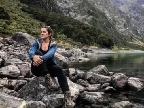 Hiker sitting on rocks surrounded by mountain and lake